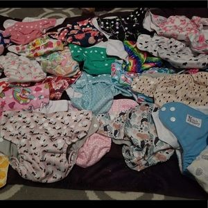 28 cloth diapers with inserts and two wet bags.